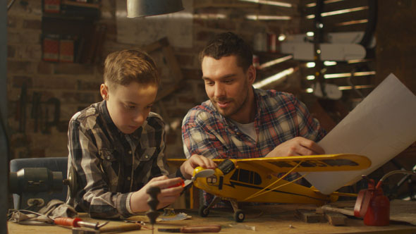 16_73_14_father_and_son_modeling_toy_airplane_in_garage